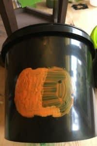 2nd-coat-of-Ogre-Orange-Peelable-Glass-Paint-on-plastic-bucket